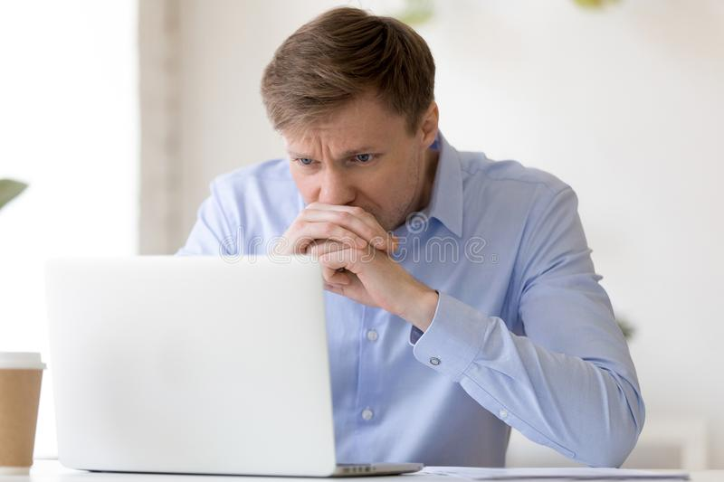 Focused businessman looking at laptop screen, thinking about bus stock photo