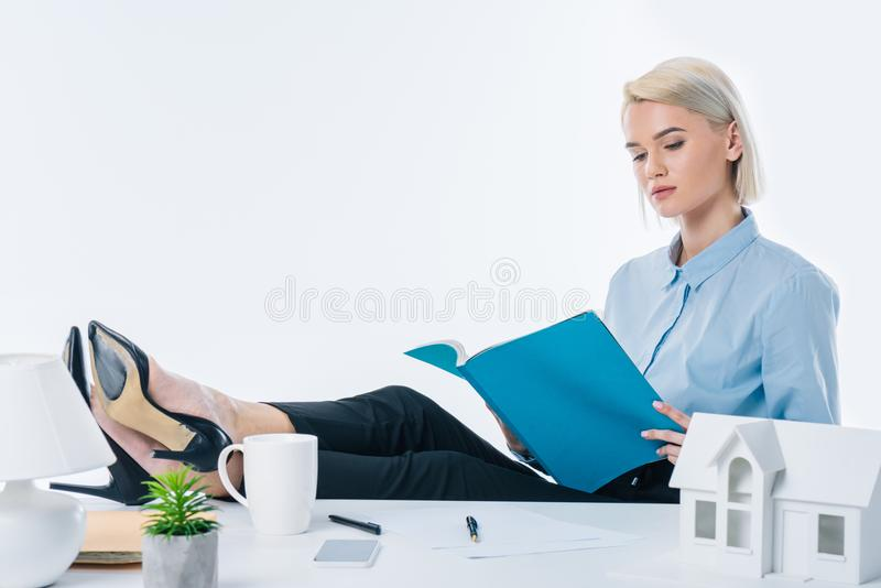 Focused real estate agent looking at notebook in hands. At workplace royalty free stock photo