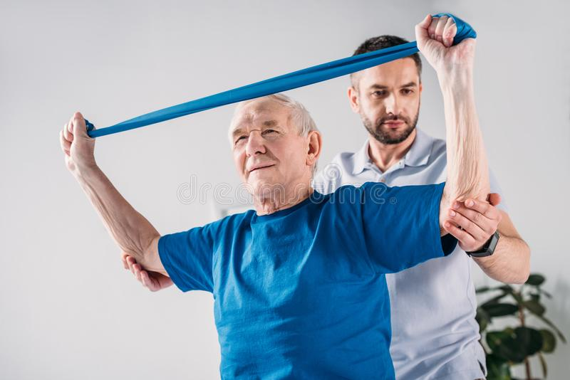 Focused rehabilitation therapist assisting senior man. Focused rehabilitation therapist assisting senior men exercising with rubber tape stock photo