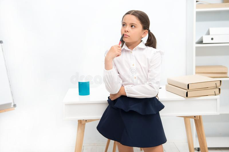 Focused on remembering. Child girl wears school uniform standing with remembering face expression. Schoolgirl smart royalty free stock photography