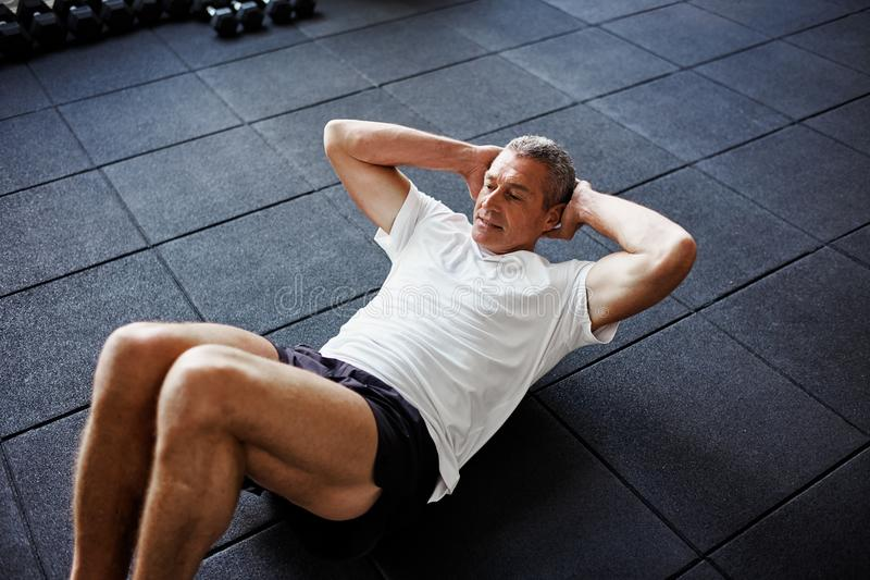 Focused senior man doing an ab workout in a gym royalty free stock image
