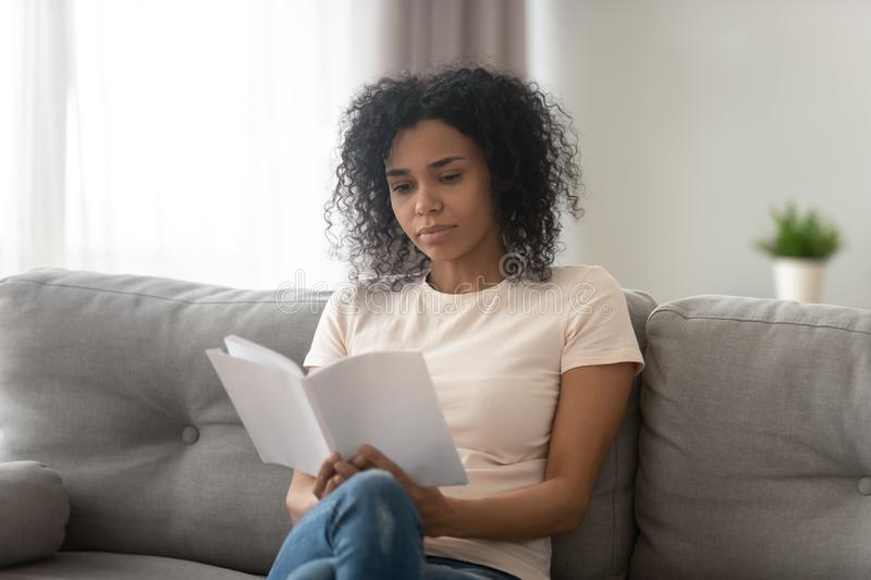 Focused serious African American woman reading book at home royalty free stock images
