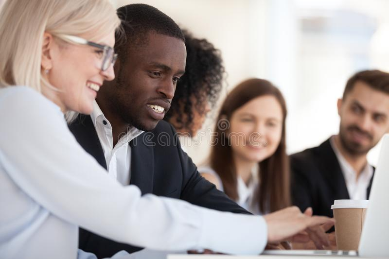 Focused smiling diverse colleagues using laptop together close up stock photos