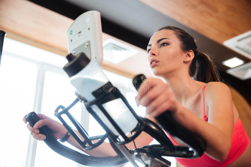 Focused sportswoman exercising on bicycle in gym royalty free stock photos