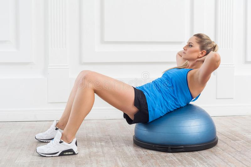Focused sporty beautiful young athletic blonde woman in black shorts and blue top working in gym doing exercises for abdominal. Muscles on bosu balance trainer stock image