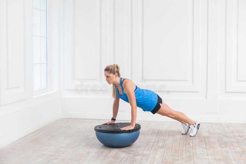Focused sporty beautiful young athletic blonde woman in black shorts and blue top working in gym doing plank for abdominal muscles. On bosu balance trainer royalty free stock images