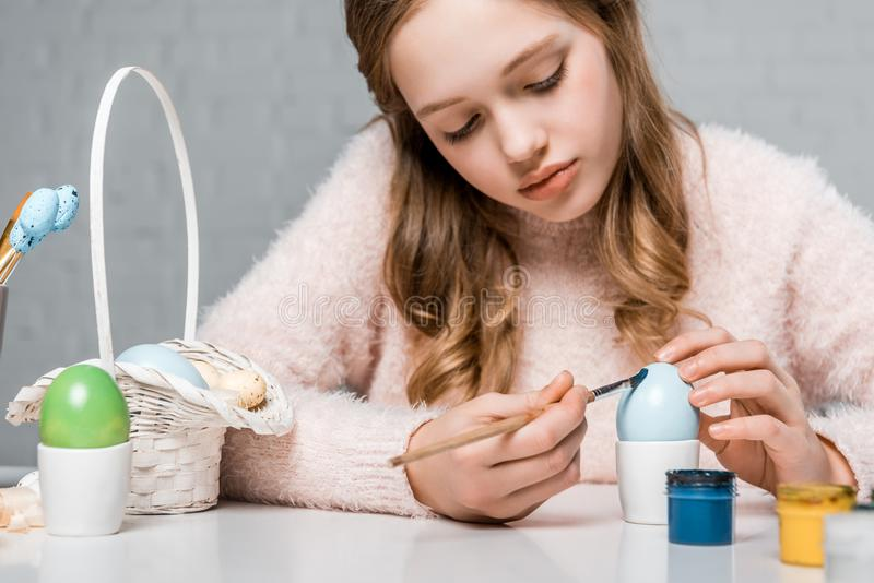 Focused teenage girl painting egg for easter stock photos
