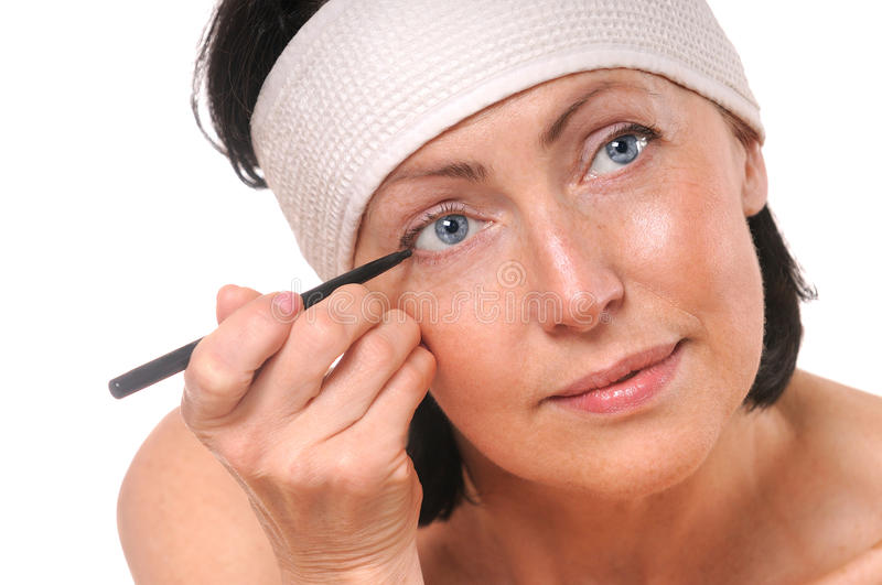 Focused woman looking at camera while putting eyeliner stock photography