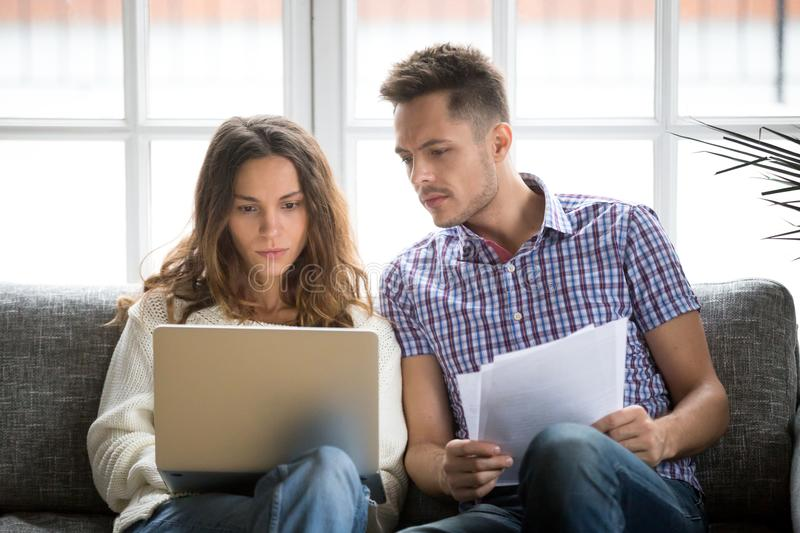 Focused worried couple paying bills online on laptop with document royalty free stock images