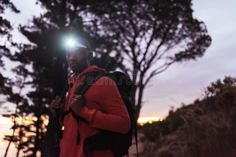 Focused young African man wearing a headlamp hiking at dusk. Portrait of a focused young African man wearing a headlamp standing alone in the forest while out royalty free stock images