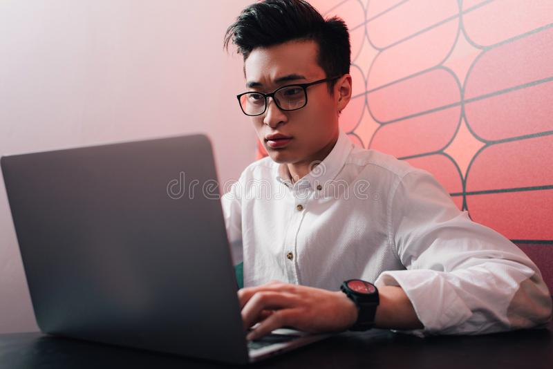 focused young asian businessman working at table with laptop royalty free stock photo