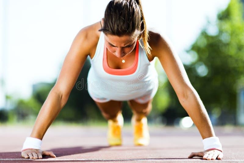 Young beautiful woman doing push-ups outdoors on a hot summer da. Focused young beautiful woman doing push-ups outdoors on a hot summer day royalty free stock image