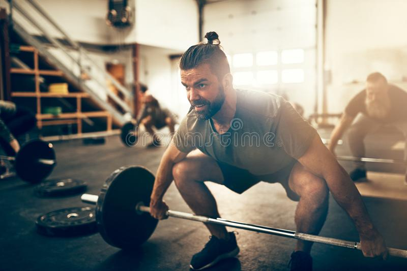 Focused young man preparing to lift weights during a workout royalty free stock image