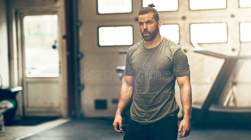 Focused young man in sportswear standing alone in a gym stock photos