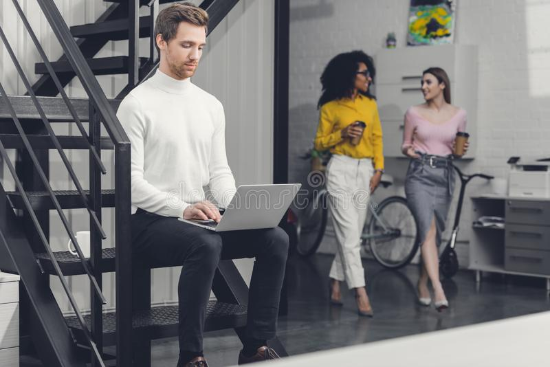 Focused young man using laptop on stairs and businesswomen walking behind royalty free stock images