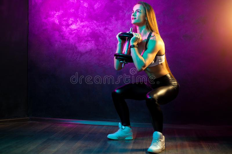 Focused young woman fitness model doing squats with professional dumbbells in neon lights silhouette in the studio. Focused young woman fitness model doing royalty free stock images