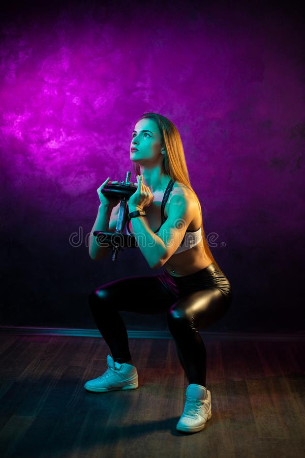 Focused young woman fitness model doing squats with professional dumbbells in neon lights silhouette in the studio. Focused young woman fitness model doing stock images