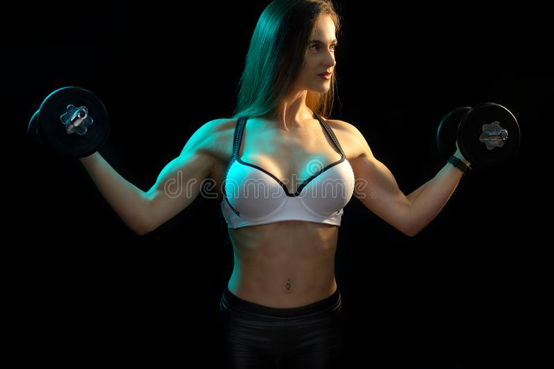 Focused young woman fitness model exercise biceps with professional dumbbells in neon lights silhouette in the studio. Focused young woman fitness model royalty free stock photo