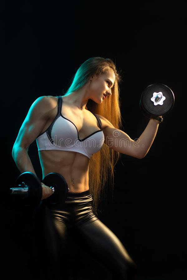 Focused young woman fitness model exercise biceps with professional dumbbells in neon lights silhouette in the studio. Focused young woman fitness model royalty free stock images