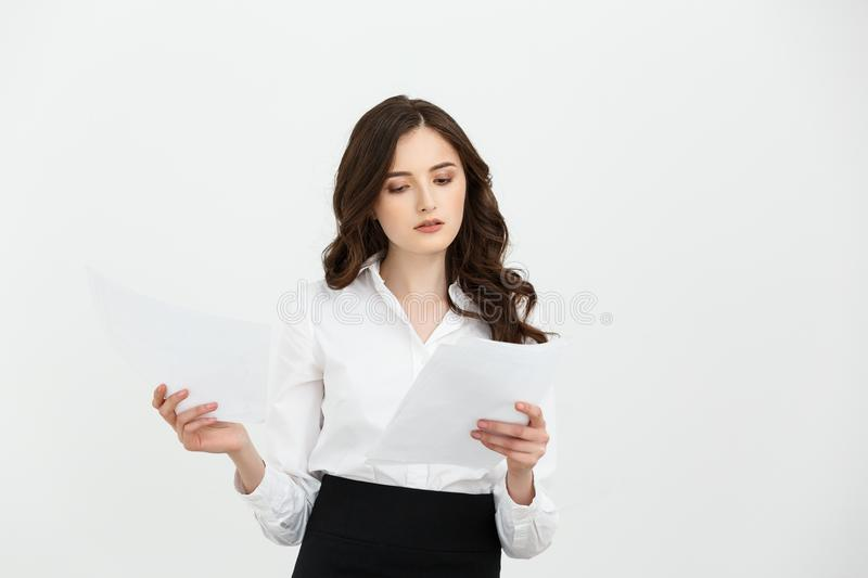 Focused young woman holding sheet of paper and reading. Document concept. front view on white background. royalty free stock images