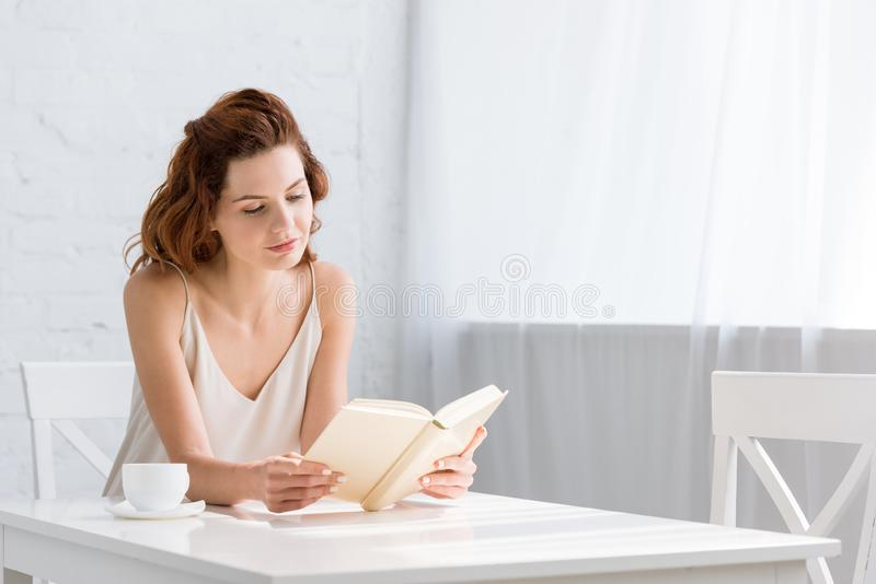 focused young woman reading book with coffee cup on table royalty free stock image
