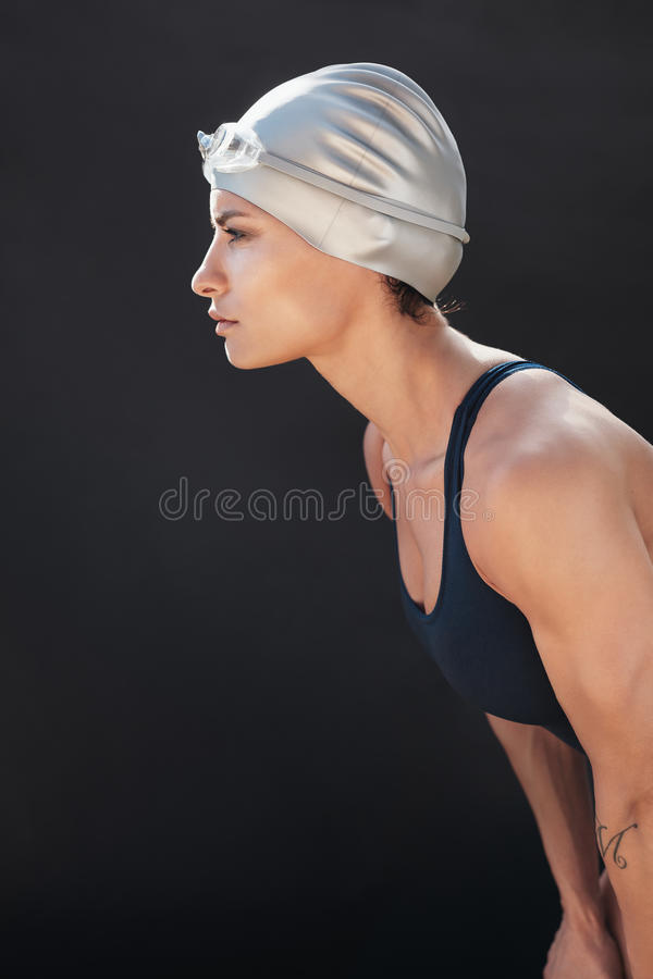 Focused young woman in swimsuit looking away. Side view of focused young woman in swimsuit looking away on black background. Determined female swimmer royalty free stock images