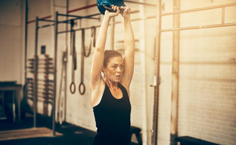 Focused young woman swinging a dumbbell at the gym stock images
