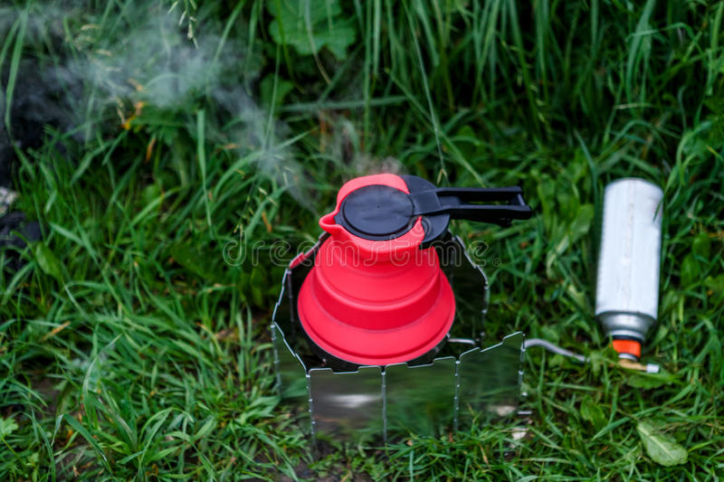 Fodable camping kettle with boiling water standing on burning stove. stock photography