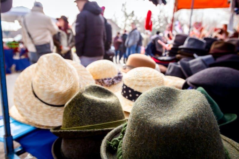 Fodrad man och kvinnliga hattar i loppmarknaden fotografering för bildbyråer