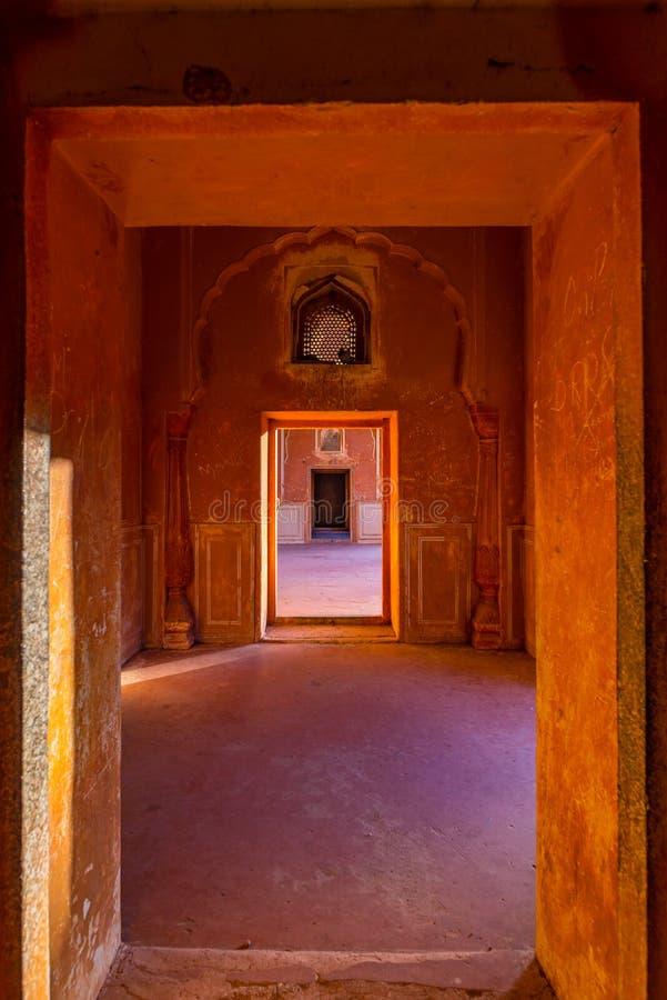 Fodrade dörrar och passager i apelsin tonade korridoren med dekorerade väggar Inre av den majestätiska Amber Fort, Jaipur, loppde arkivbild