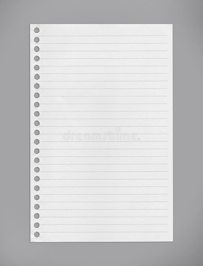 Fodrat anteckningsbokpapper på grå bakgrund/snabba banor arkivbilder