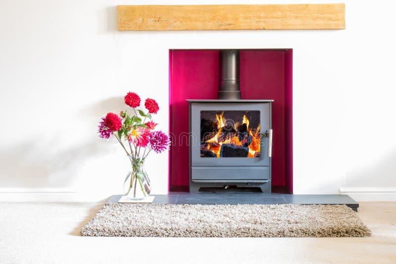 Fogão ardente de madeira com fogo de log de ardência em uma sala branca com fl fotografia de stock royalty free