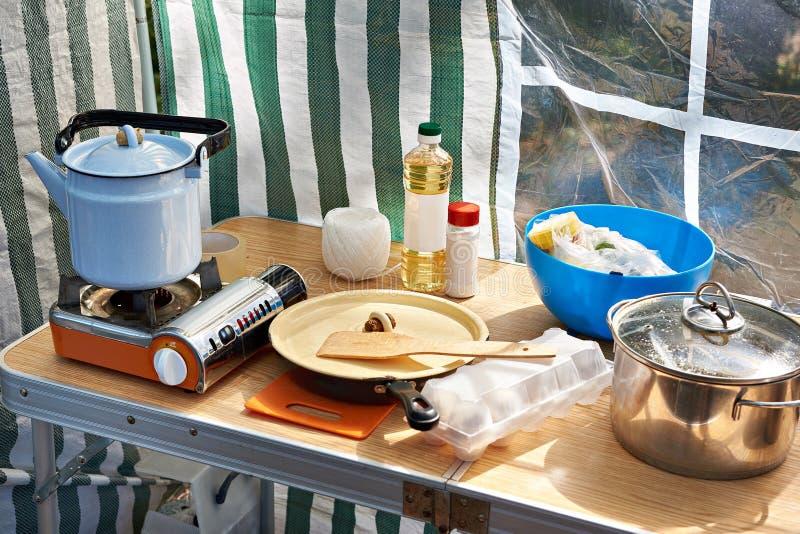 Fogão de acampamento com chaleira e louça na tabela foto de stock