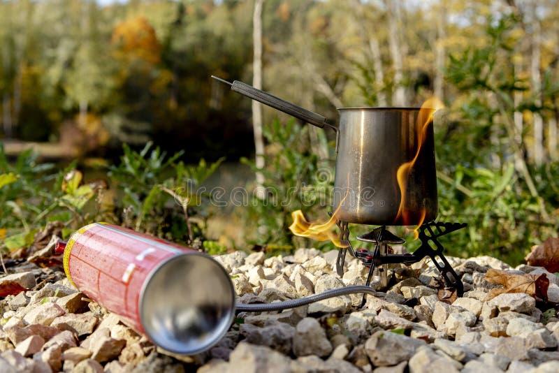 Fogão de gás portátil do turista com uma chaleira cinzenta em um fundo da natureza nas montanhas Cozinha e chá de acampamento fotos de stock