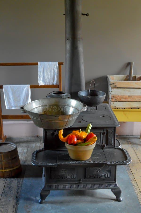 Fogão de madeira do ferro fundido com a cesta dos vegetais foto de stock