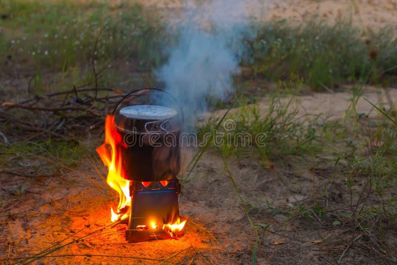 Fogão de madeira portátil de queimadura com um caldeirão imagens de stock
