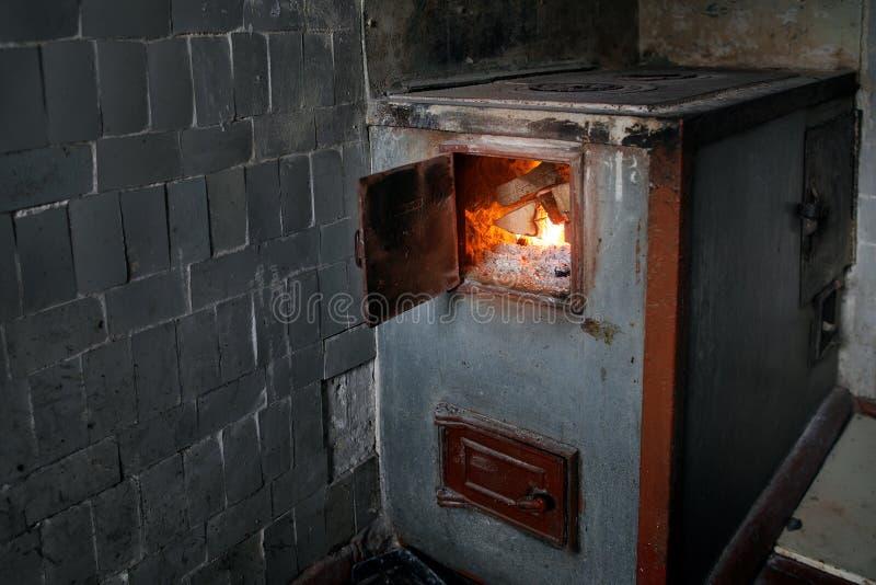 Fogão de madeira rural velho com a lenha ardente imagem de stock