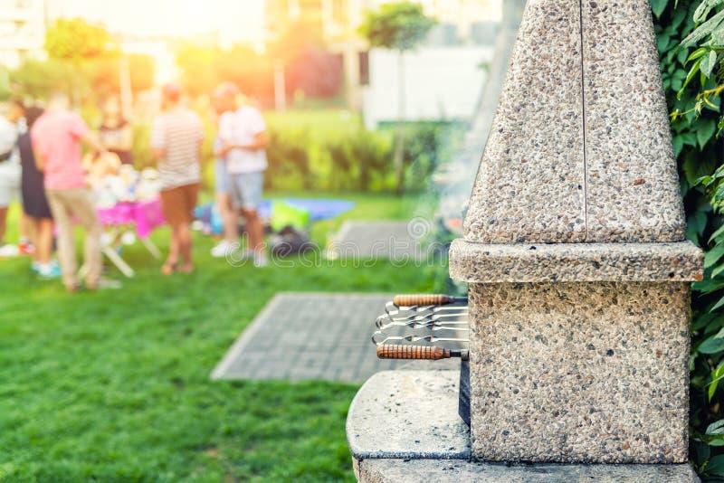 Fogão de pedra exterior com grade e espetos Empresa dos amigos no partido do assado no parque ou no quintal com gramado da grama  imagem de stock royalty free