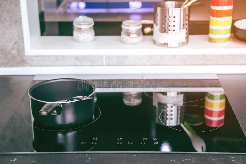 Fogão elétrico A frigideira é colocada em um fogão elétrico moderno, fogão preto da indução, fogão imagens de stock