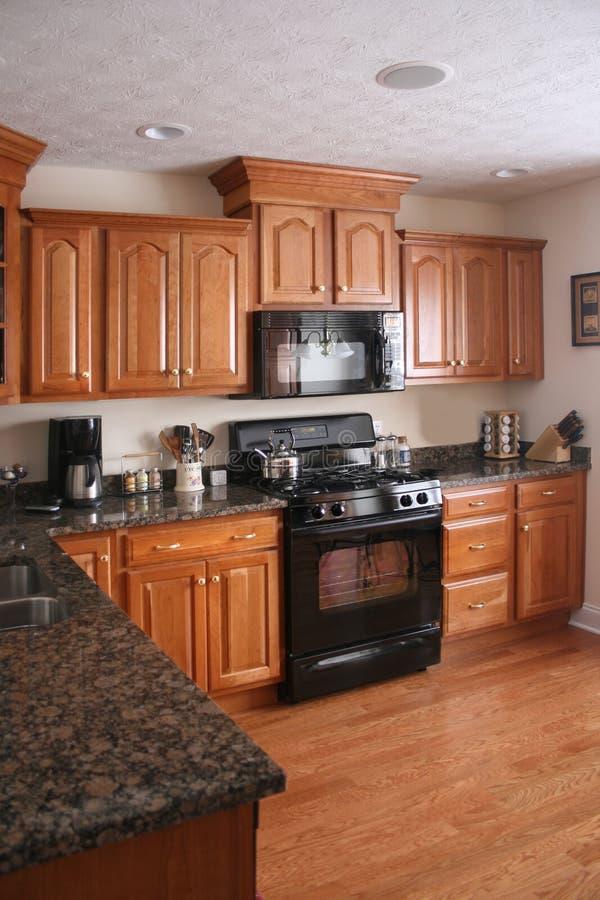 Fogão preto dos gabinetes de madeira da cozinha foto de stock