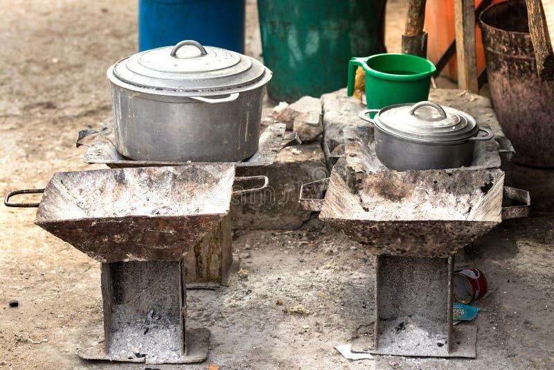 Fogões e cookware rústico do carvão vegetal, potenciômetros e bandejas no assoalho no mercado local de Toliara, Madagáscar fotografia de stock royalty free