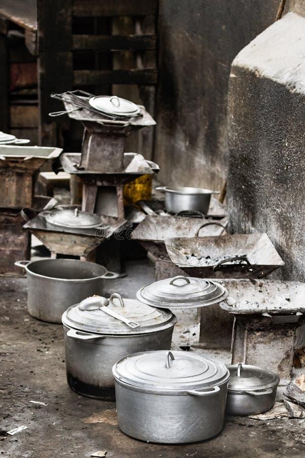 Fogões e cookware rústico do carvão vegetal, potenciômetros e bandejas no assoalho no mercado local de Toliara, Madagáscar foto de stock royalty free