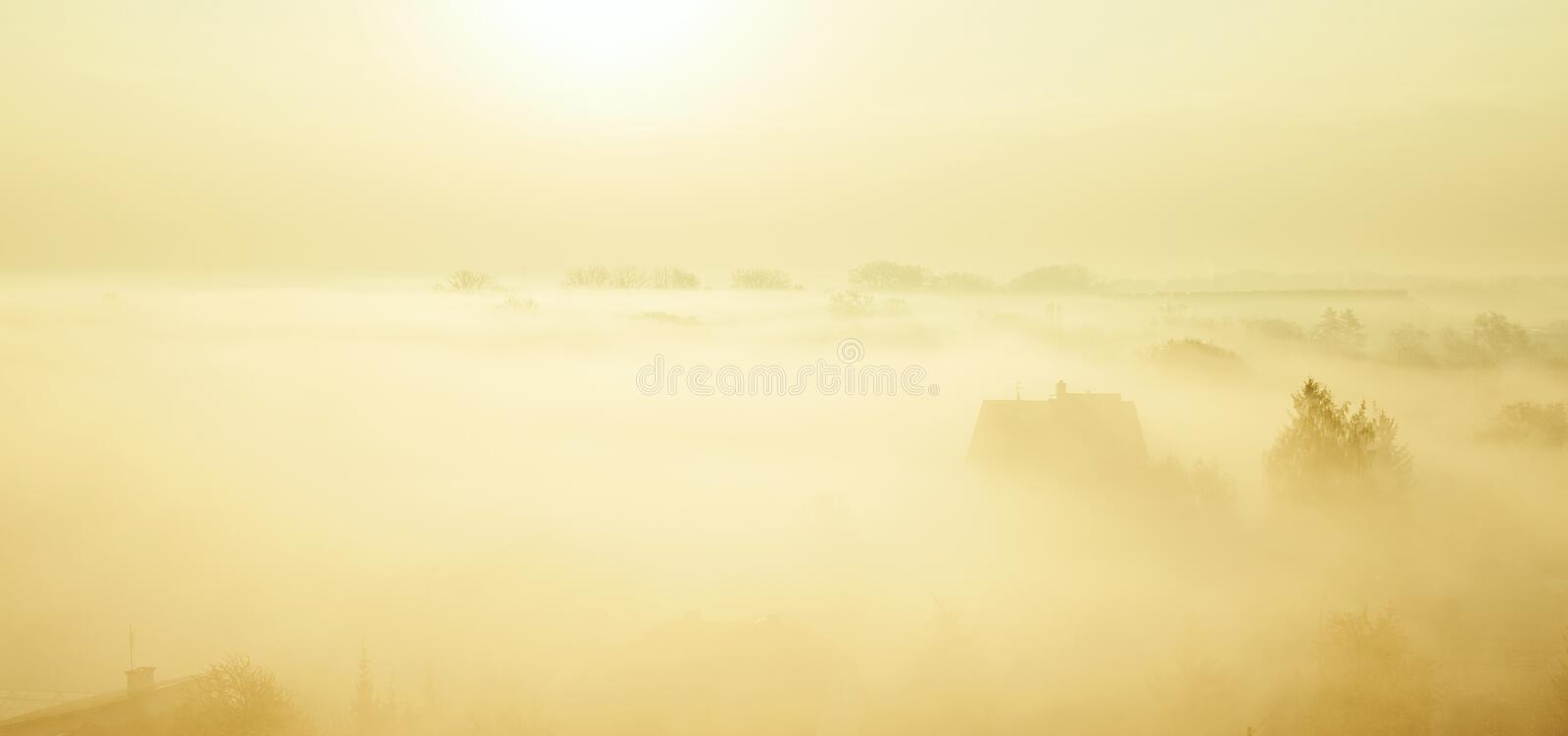 Fog. Gy morning with silhouettes of houses in creamy pastel color tone royalty free stock photo