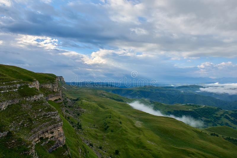 Fog above a green mountain valley under beautiful cumulus clouds at sunrise stock photo