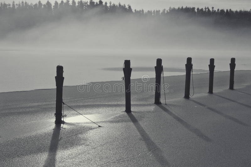 Fog Bank Over the Icy Lake. Black and white shot of fog bank over a lake. Mooring post in focus stock images