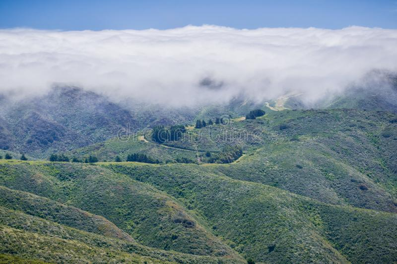Fog covering the hills and valleys of Montara mountain McNee Ranch State Park landscape, California stock image