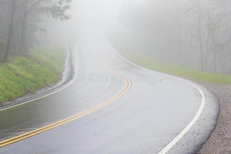 Fog Covers Curving Smoky Mountain Road With Copy Space. Horizontal shot of fog covering a curving Smoky Mountain Road with copy space royalty free stock image
