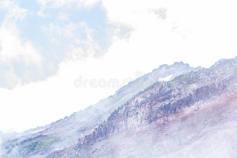 Fog create layers of mountain view in soft purples and blues. Stone trees and fog create layers of mountain view in soft purples and blues near mount rainier stock image