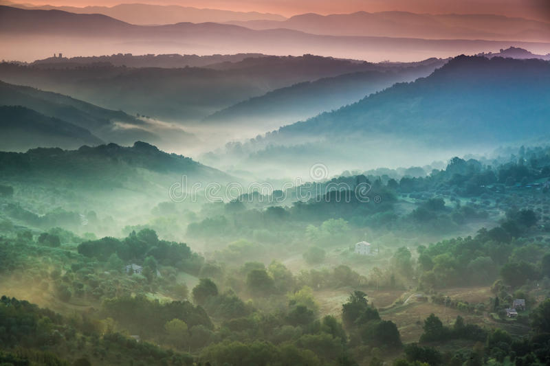 Fog at dawn over the valley in Tuscany royalty free stock image