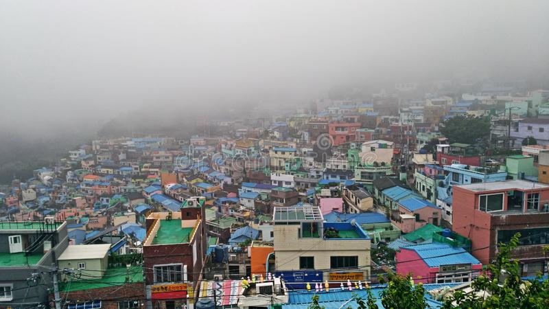 The fog does not spoil the colors. Asia travel, South Korea, Busan, view from above of the characteristic neighborhood Gamcheon Cultural Village, a thick fog stock photo